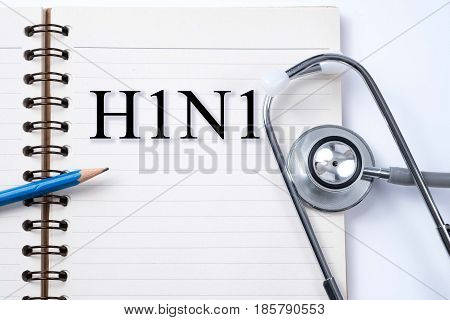 Notebook pencil and stethoscope with words H1N1 diseases.