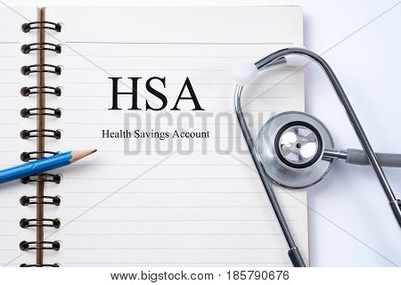 Notebook and pencil with HSA (Health Savings Account) on the table with stethoscope medical concept