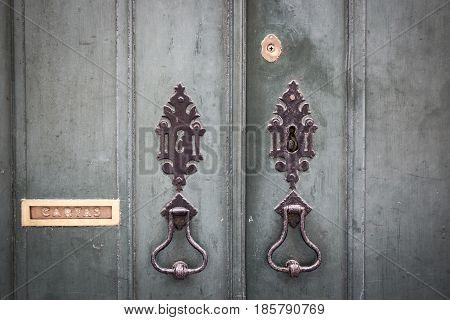 ancient door knockers, lock and a mailbox of an ancient green wooden door
