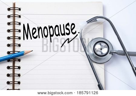 Stethoscope on notebook and pencil with menopause words as medical concept