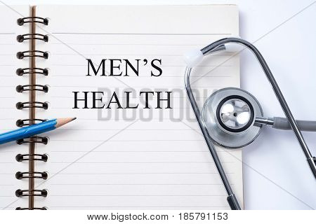 Notebook and pencil with Men's health on the table with stethoscope medical concept