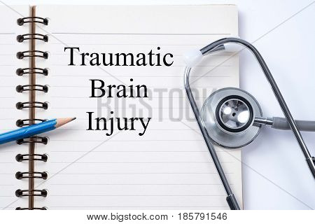 Stethoscope on notebook and pencil with traumatic brain injury words as medical concept.