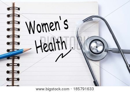 Stethoscope on notebook and pencil with women's health words as medical concept