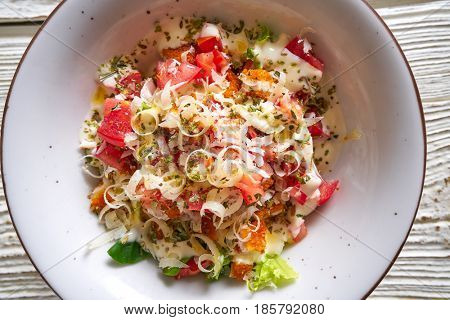 Cesar caesar salad with tomato cheese lettuce and sauce