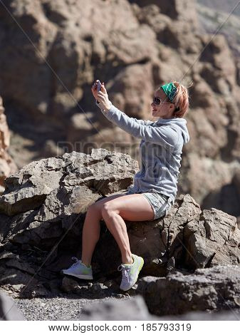 Young female traveler taking selfie on the beautiful rocky background in Teide Natural Park , Tenerife island, Canary islands, Spain