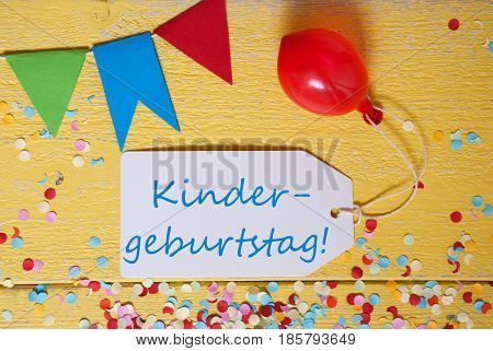 White Label With German Text Kindergeburtstag Means Children Birthday Party. Party Decoration Like Streamer, Confetti And Balloon. Flat Lay Or Top View. Yellow Wooden Background