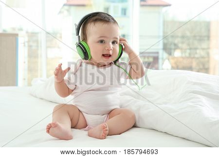 Cute little baby with headphones at home