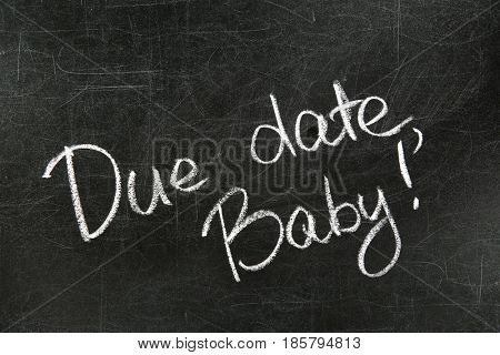 Words DUE DATE, BABY written with chalk on blackboard