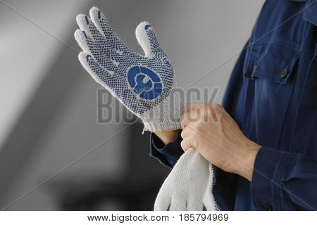 Hands of auto mechanic putting on gloves in car repair shop