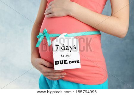 Card on belly of pregnant woman with inscription 7 DAYS TO MY DUE DATE