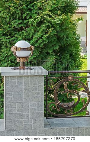 A spherical street lamp and forged railing which is installed near the entrance doors or adorns the infield