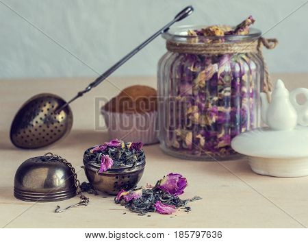 Tea strainer closeup tea leaves and rose buds glass jar selective focus