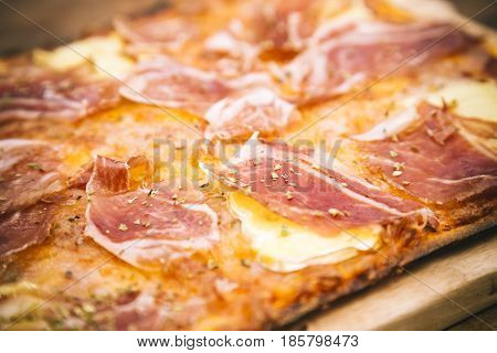Detail of rustic ham and brie cheese pizza sprinkled with provencal herbs