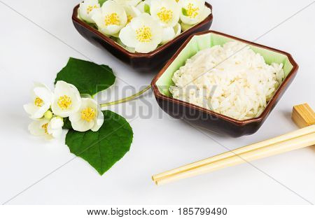 Healthy Eating Concept Eco dish with jasmine rice and jasmine flowers on a white background