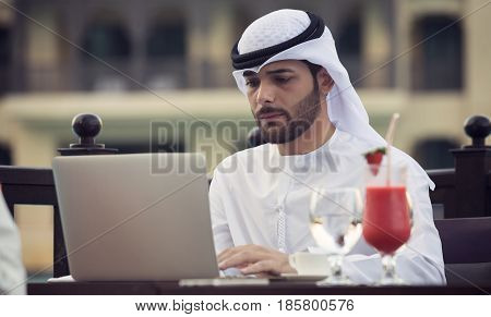 Arab young businessman working with laptop in cafe