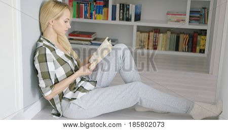 Young woman wearing home clothing and sitting on floor with book on background of shelves with books.