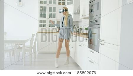 Young girl in grey sweat shirt wearing VR glasses and standing among light and modern kitchen alone.