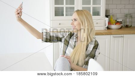 Young smiling woman in checkered shirt sitting on chair near table and taking self portrait in kitchen.