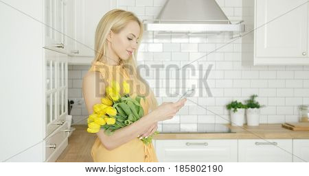 Side view of young beautiful girl holding bouquet of yellow tulips using phone on background of kitchen.