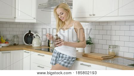 Young attractive woman wearing home clothing and standing in modern kitchen eating chocolate spread from jar.