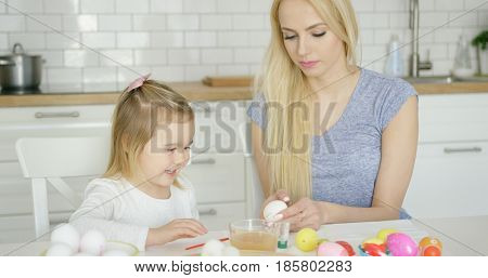 Laughing little girl coloring Easter egg with help of young mother while sitting at table at kitchen.