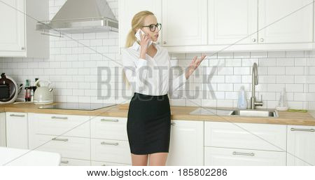 Beautiful confident woman in formal outfit and glasses talking by smart phone while standing at modern kitchen.