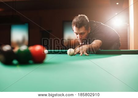 Player breaks a pyramid in billiards. Nightlife. Billiard room on the background.
