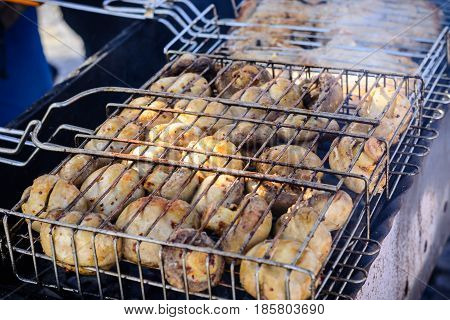Champignon white mushrooms grilled on grill or barbecue in smoke the heat of the coals