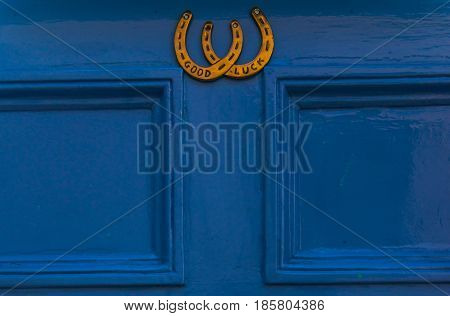 Blue Wooden Door To House With A Brass Knocker In The Shape Of Horseshoes, With The Words Good Luck