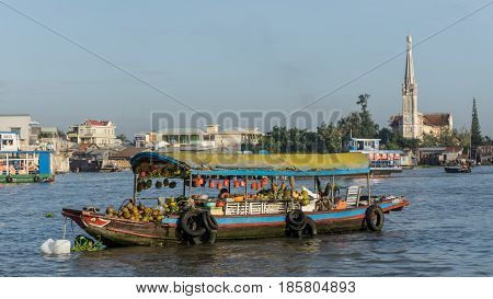 Mekong, Vietnam - November 29, 2015: A boat from Floating market, with The Catholic Church in Mekong Delta in background.