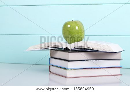 stack of books on a turquoise background and green apple. love of reading