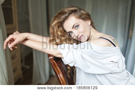 Beautiful young woman with long red curvy hair leaning on the back of the chair