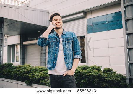 Young man standing outdoors and talking on the phone. He is happy to hear some interesting information from his friends