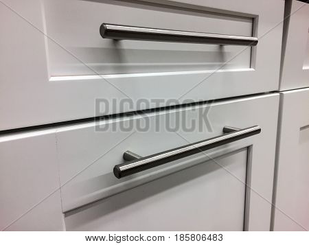 White kitchen cabinets. Modern base cabinets with metal handles. Modern Cabinets. Contemporary Italian kitchen cabinet design. Stainless steel handles on doors and drawers of wooden kitchen cabinet.