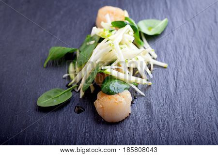 Scallop salad with apple, spinach on a stone plate