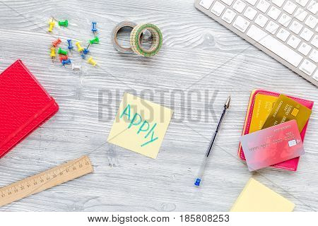 admission fee-paying school with credit cards, keyboard and notebook on white desk background top view