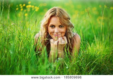 blonde young woman lays on green grass