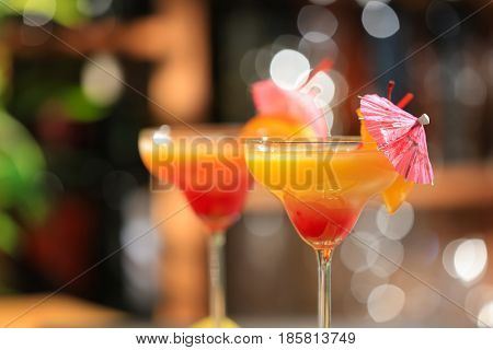 Tequila Sunrise cocktail in glass on blurred background