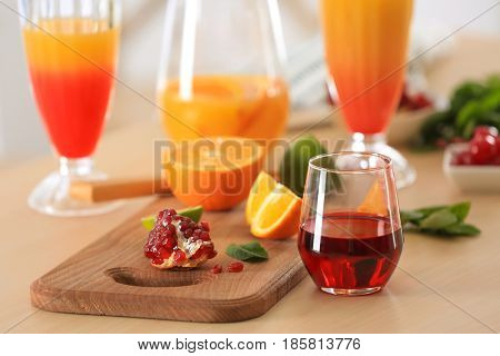 Glasses of Tequila Sunrise cocktail with ingredients on kitchen table