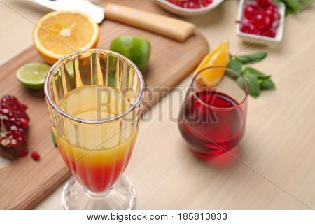 Glass of Tequila Sunrise cocktail and ingredients on table