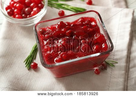 Delicious cranberry sauce in glass bowl on wooden background