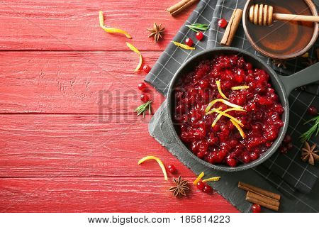 Delicious cranberry sauce in pan on wooden background, top view