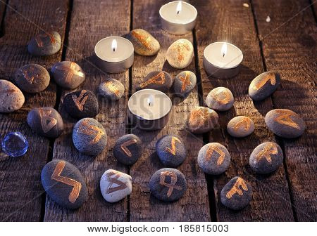 Mystic still life with stone runes and candles. Halloween background, black magic rite or spell, occult and esoteric objects on witch table