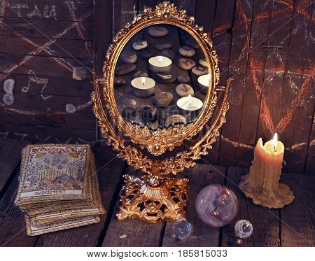 Magic mirror with Tarot cards and burning candles. Halloween background, black magic rite or spell, occult and esoteric objects on witch table