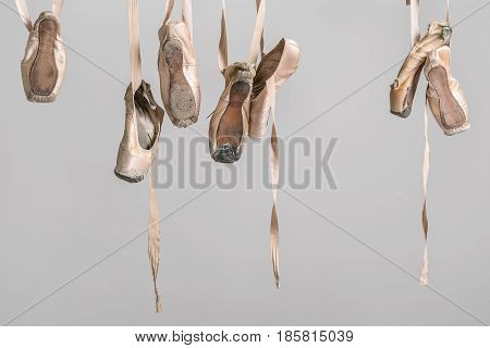 Seven hanging beige ballet shoes on the gray background in the studio. Closeup. Horizontal.