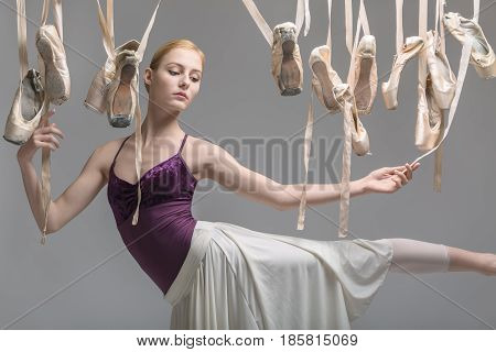 Pretty ballerina in a violet top and a cream skirt posing on the gray background in the studio. Around her there are many hanging beige pointe shoes. She holds ribbons of the ballet shoes.