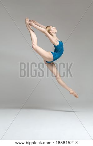 Tender ballerina posing in the jump on the gray background in the studio. She wears a blue leotard. Her legs and arms stretched to the sides. Shoot from the side. Vertical.