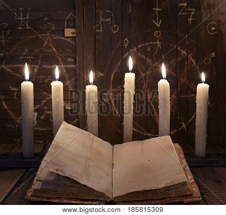 Black magic ritual with burning candles and open book against wooden background. Halloween still life, black magic rite or spell, occult and esoteric objects on witch table