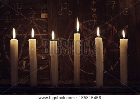 Mystic close up with burning candles against wooden background with pentagram. Halloween background, black magic rite or spell, occult and esoteric objects on witch table