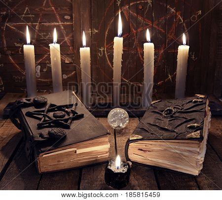 Esoteric still life with black magic book and burning candles. Halloween background, black magic rite or spell, occult and esoteric objects on witch table